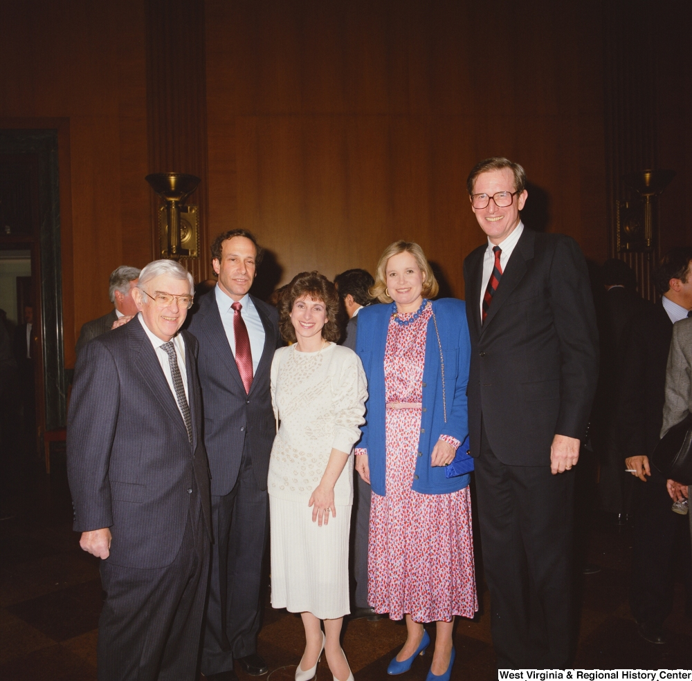 "[""Senator John D. (Jay) Rockefeller and Sharon Rockefeller stand for a photograph with several unidentified individuals at an event at the Senate.""]%"