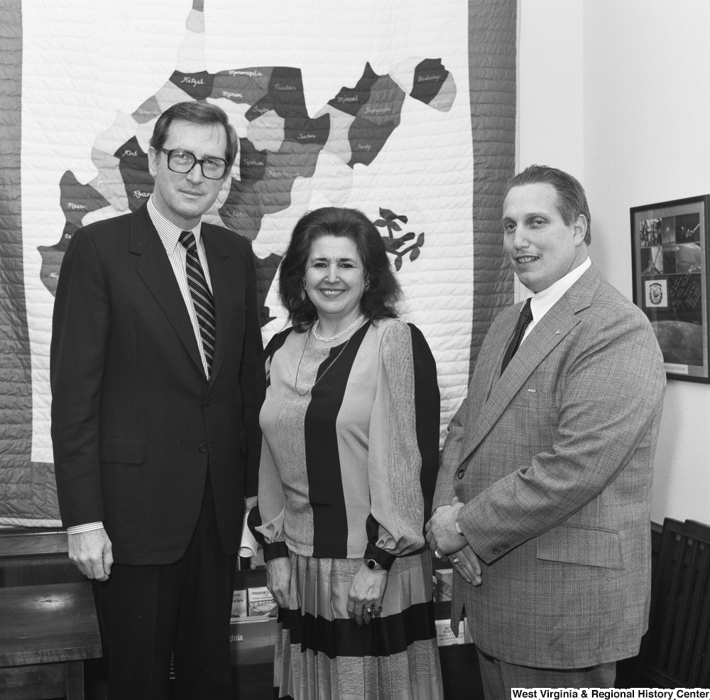 "[""Senator John D. (Jay) Rockefeller poses for a photograph with a woman from the Department of Employment Security and a man from Elkins Iron in his Washington office.""]%"