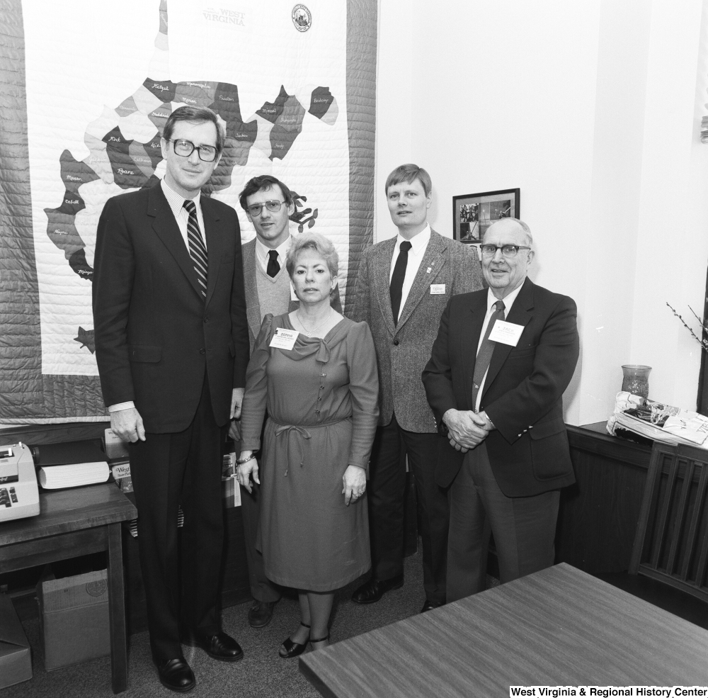 "[""Senator John D. (Jay) Rockefeller stands for a photograph with a representative from Wheeling's Oglebay Resort and three other unidentified individuals in his Washington office.""]%"