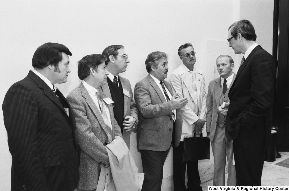 "[""Senator Rockefeller listens to an unidentified group of unemployed miners in the hallway of a Senate office building.""]%"