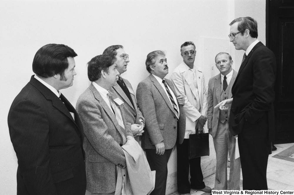 "[""Senator John D. (Jay) Rockefeller speaks to an unidentified group of unemployed miners in the hallway of a Senate office building.""]%"
