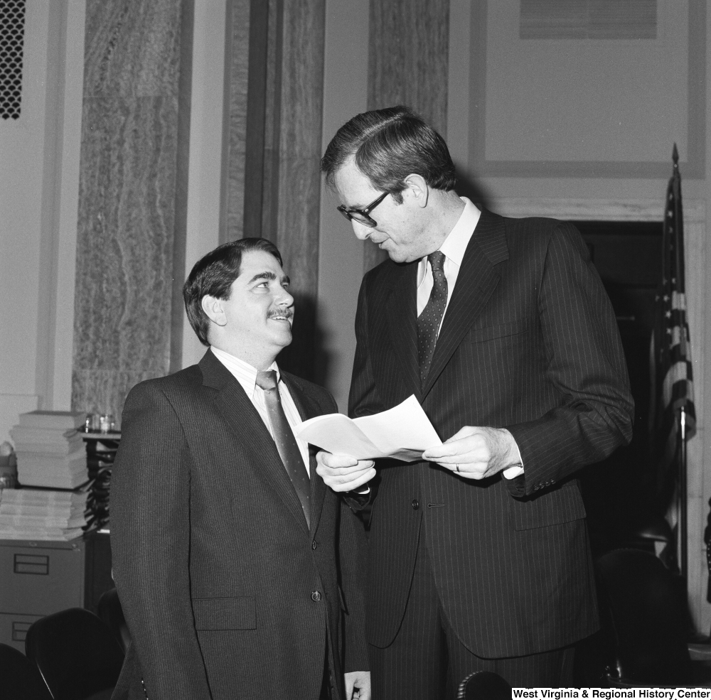 "[""Senator John D. (Jay) Rockefeller holds a sheet of paper and talks to an unidentified man in a Senate office.""]%"