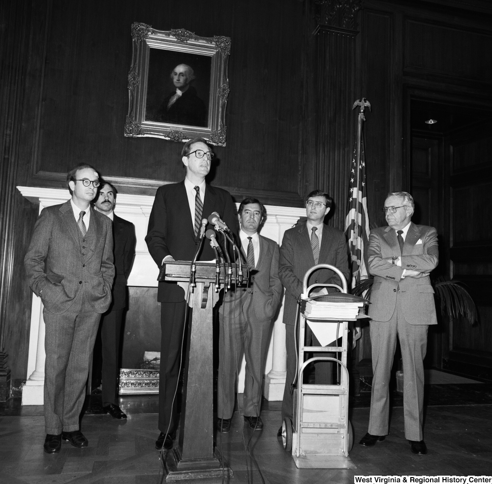"[""Senator John D. (Jay) Rockefeller speaks behind a podium at a press event for the Staggers Rail Reform in a Senate building. Congressmen Nick Rahall and Bob Wise stand behind him with who appear to be Lane Bailey, Rockefeller's State Director, and Tim Gay, Rockefeller's Press Secretary.""]%"