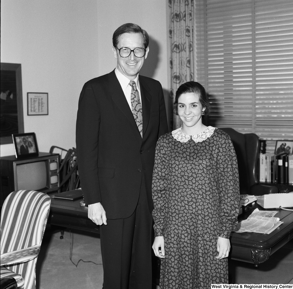 "[""Senator John D. (Jay) Rockefeller stands next to an unidentified young woman in his office.""]%"