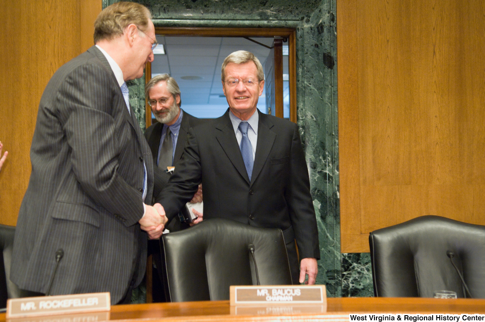 "[""Senator John D. (Jay) Rockefeller shakes hands with Senator Max Baucus as he approaches his chair at a Senate Finance Committee hearing.""]%"