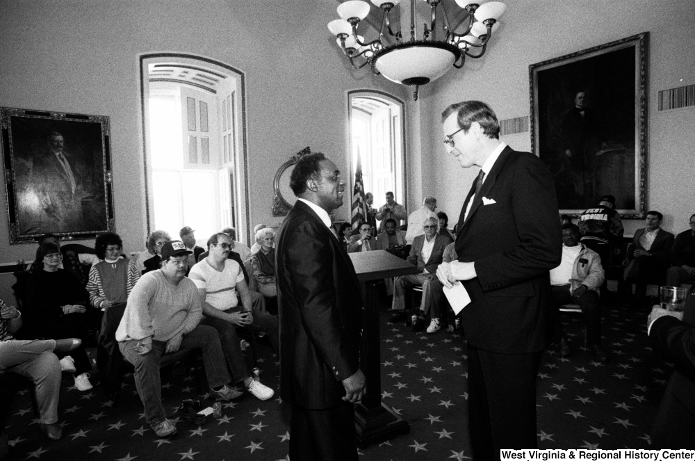 "[""Senator John D. (Jay) Rockefeller speaks with a man before addressing a room full of people in the Senate.""]%"