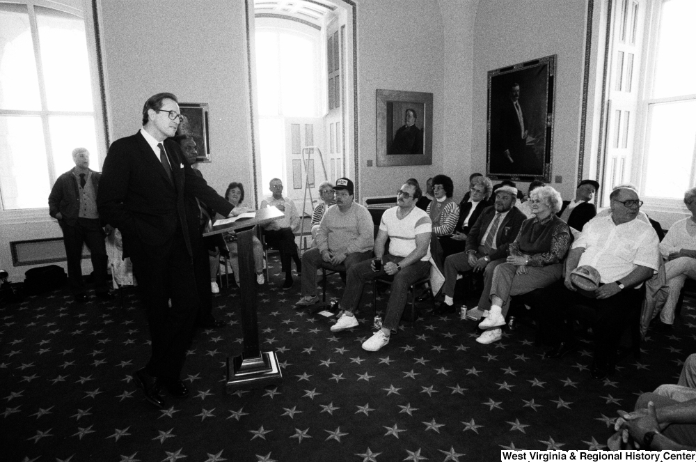"[""Senator John D. (Jay) Rockefeller stands before a group of people at a meeting about the problem of black lung disease in West Virginia.""]%"