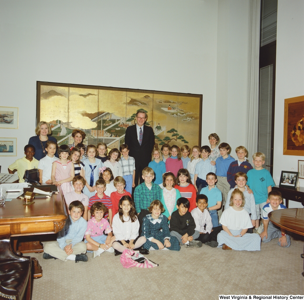 "[""Senator John D. (Jay) Rockefeller stands in his office with his wife and a group of young school children.""]%"