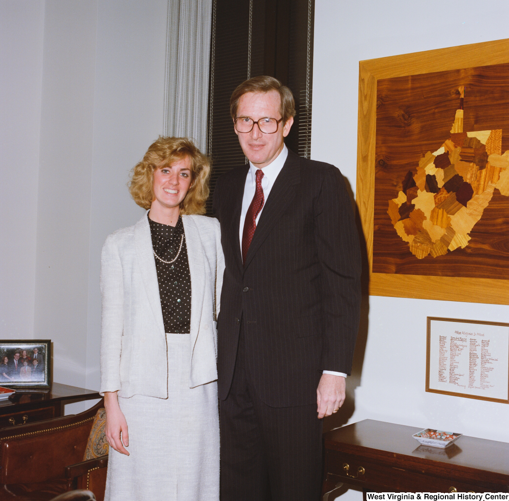 "[""Senator John D. (Jay) Rockefeller stands with an unidentified young woman in his office.""]%"