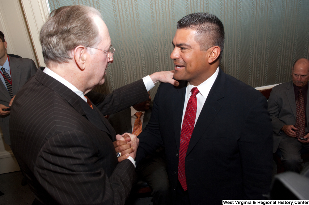 "[""Senator John D. (Jay) Rockefeller shakes hands with an unidentified man at an event to honor Bobby Cox.""]%"