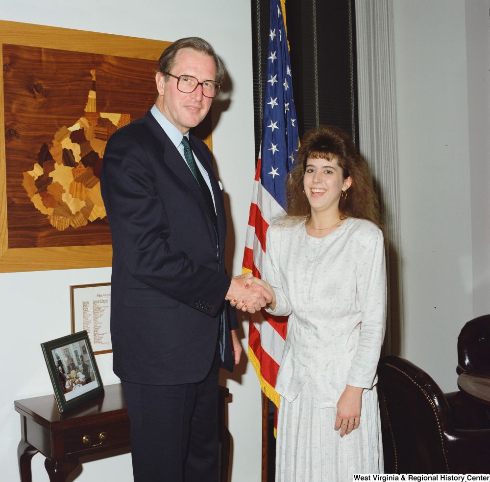 "[""Senator John D. (Jay) Rockefeller shakes hands with a young woman in his office.""]%"