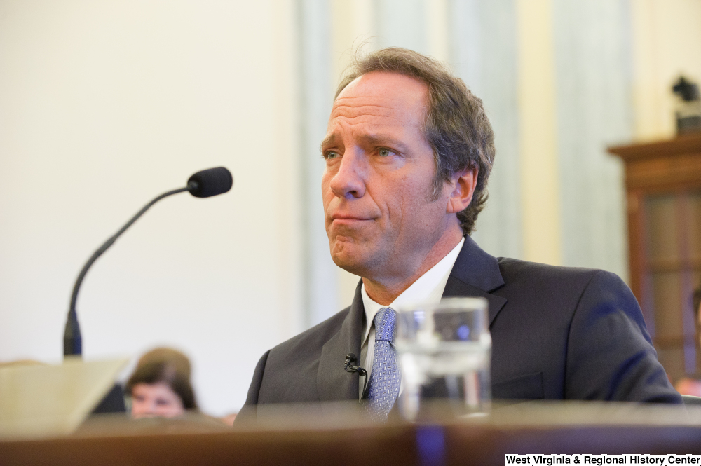 "[""Mike Rowe sits at a Senate Commerce Committee hearing.""]%"