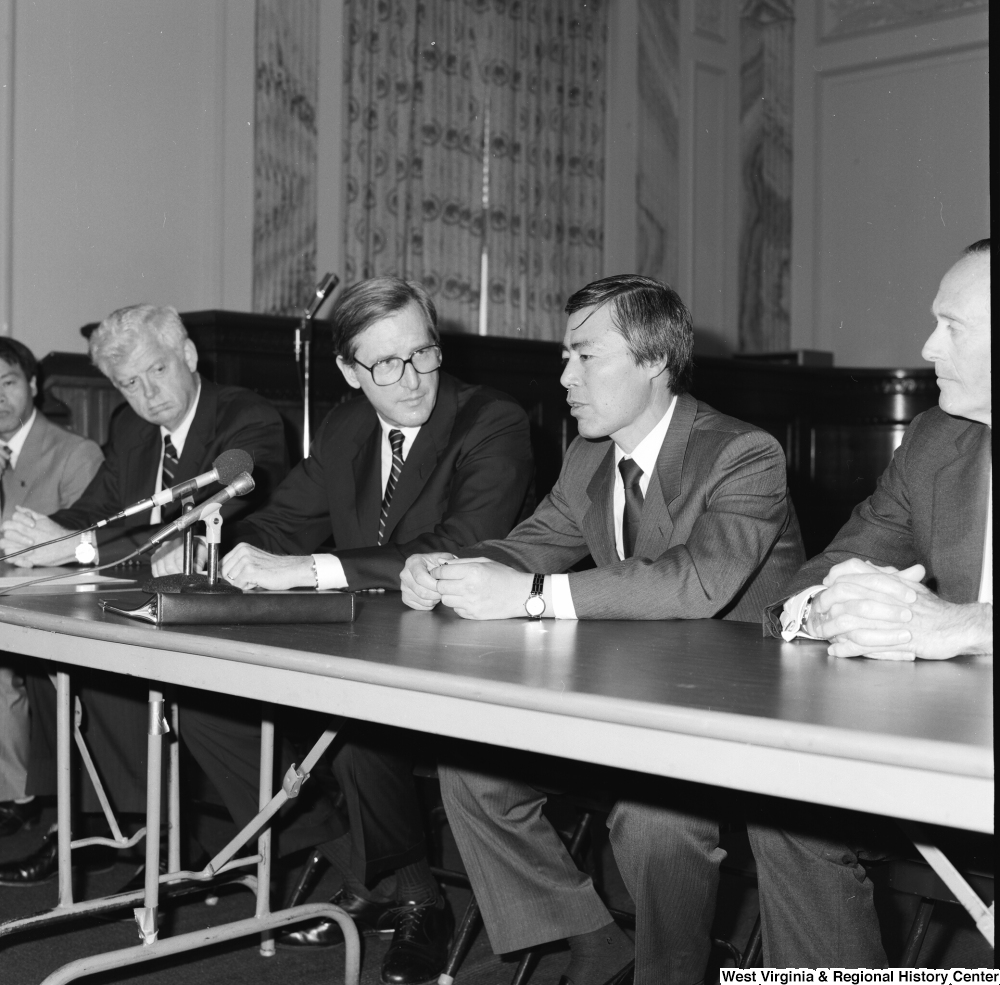 "[""Senator John D. (Jay) Rockefeller sits behind a table in the Senate at a press event.""]%"