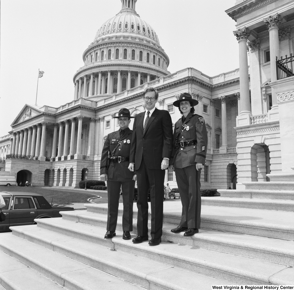 "[""Senator John D. (Jay) Rockefeller stands on the steps of the Senate with two West Virginia State Troopers""]%"
