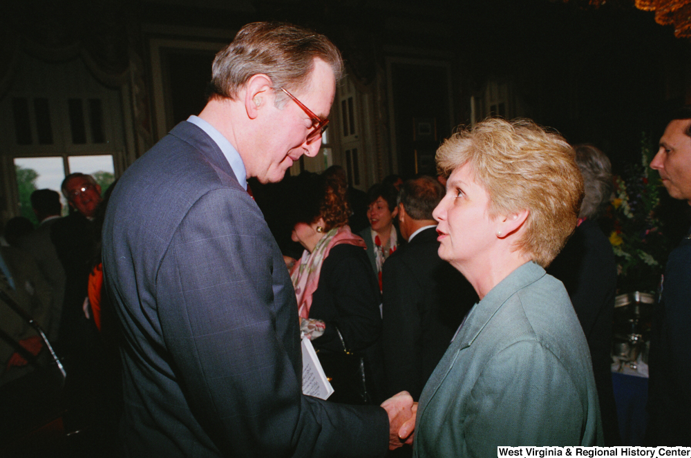 "[""Senator John D. (Jay) Rockefeller shakes hands with a woman at the Celebrating Telemedicine conference.""]%"