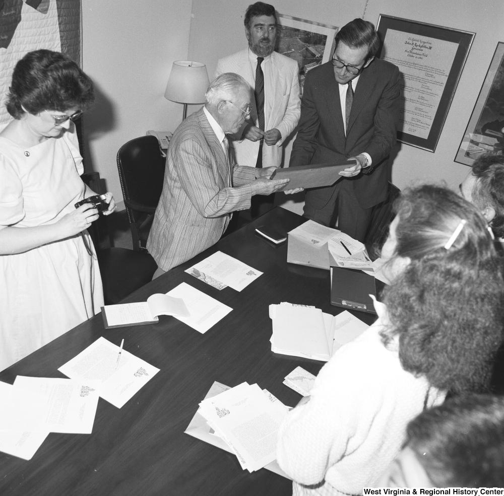 "[""Senator John D. (Jay) Rockefeller stands around a conference table and holds a photo that one of the unidentified individuals has given him.""]%"