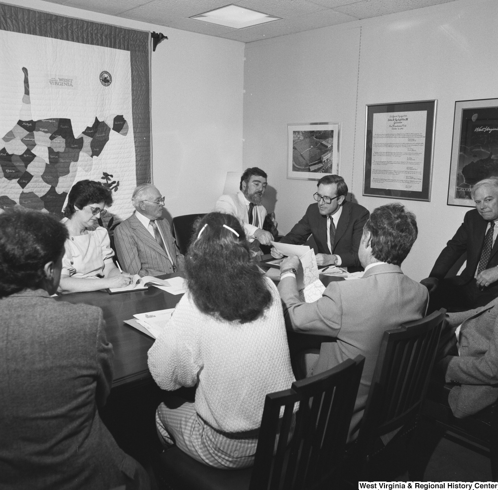 "[""Senator John D. (Jay) Rockefeller looks at a document as he sits around a conference table at a planning meeting for the Blackwater Canyon Railroad project.""]%"