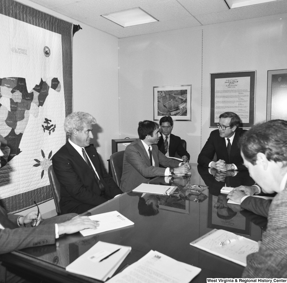 "[""Senator John D. (Jay) Rockefeller sits at a conference table in his office with several unidentified men.""]%"