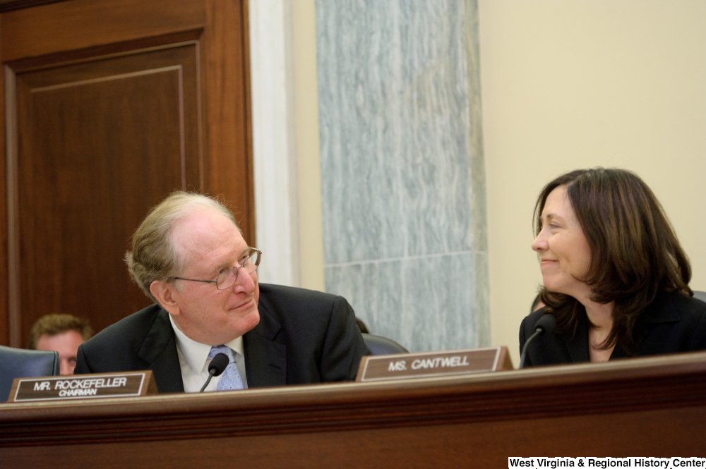 "[""Senators John D. (Jay) Rockefeller and Maria Cantwell smile at one another during a Commerce Committee hearing.""]%"