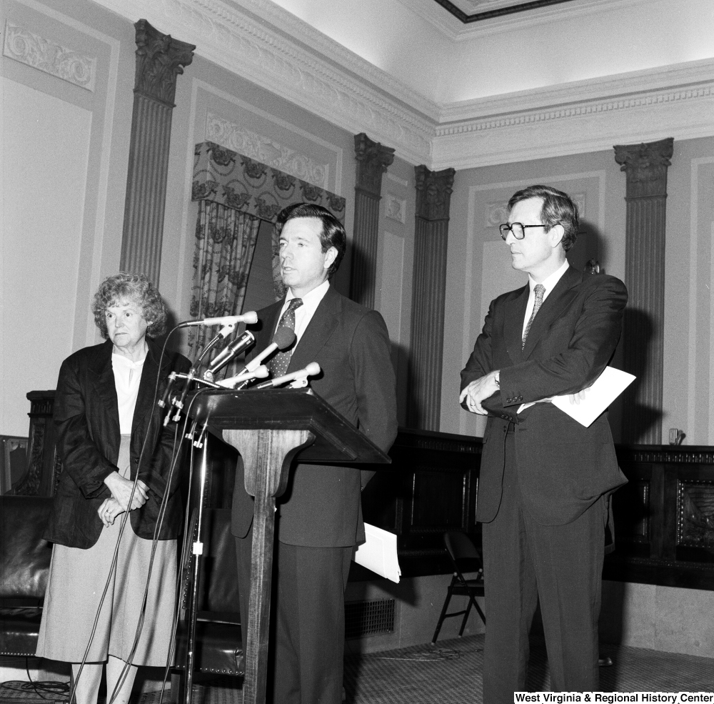 "[""Senator John D. (Jay) Rockefeller and an unidentified woman stand behind Senator John Heinz as he speaks about the Dislocated Workers Improvement Act of 1987.""]%"