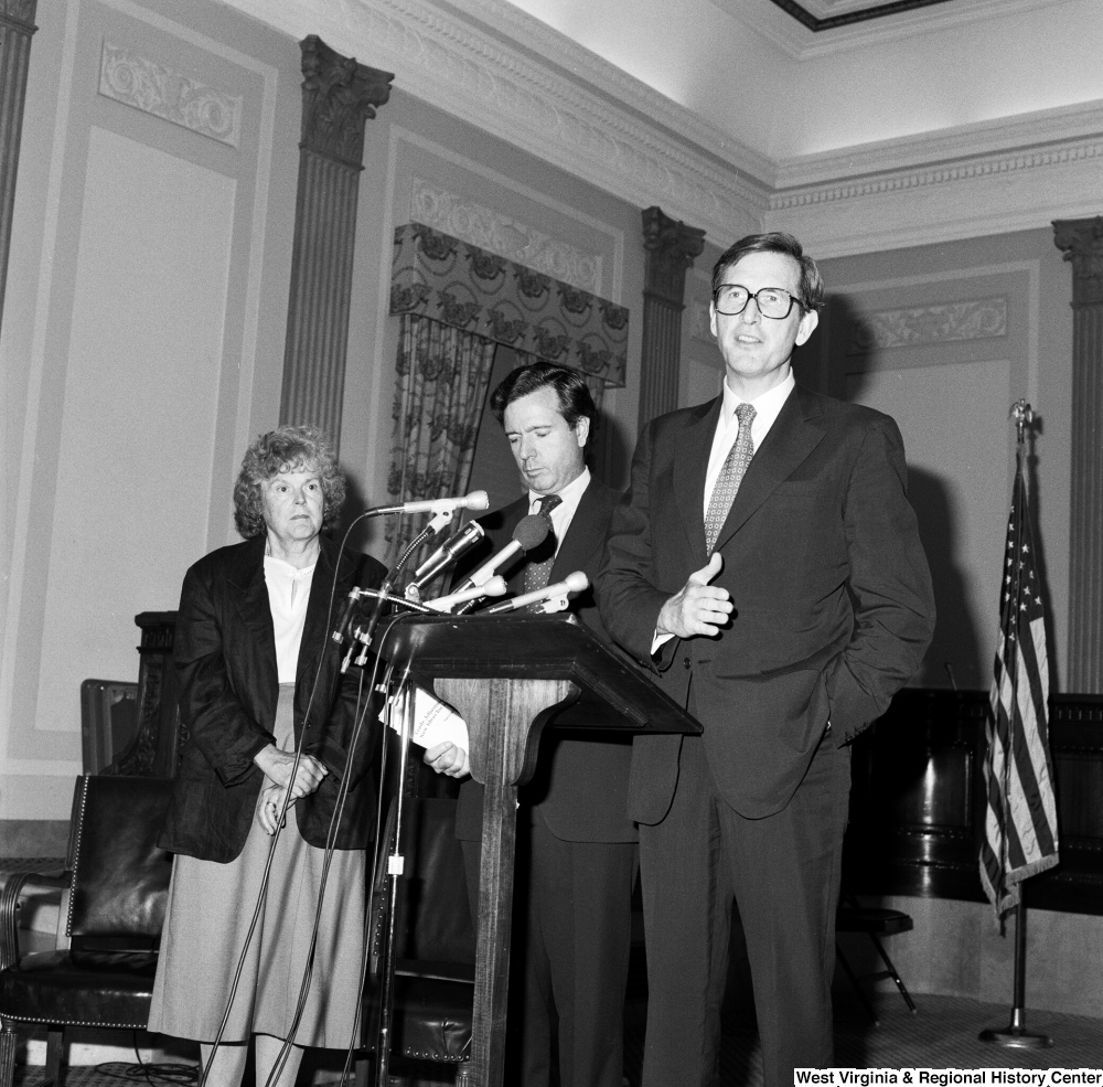 "[""Senator John D. (Jay) Rockefeller speaks about the Dislocated Workers Improvement Act of 1987 while Senator John Heinz and an unidentified woman stand next to him.""]%"