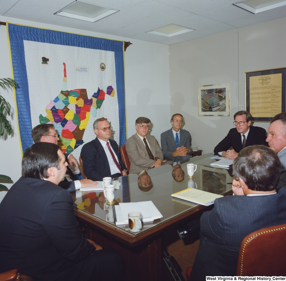 "[""Senator John D. (Jay) Rockefeller sits at a conference table with several unidentified men during a Kammer Tall Stacks meeting.""]%"