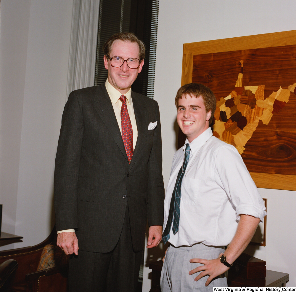 "[""Senator John D. (Jay) Rockefeller stands next to one of his interns.""]%"