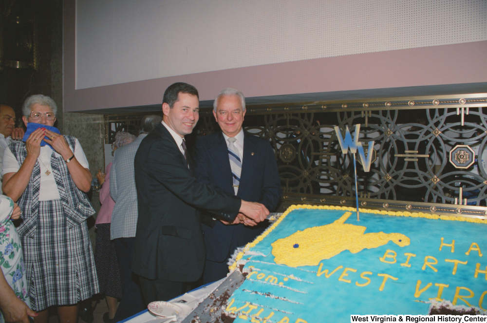 "[""Senator Robert C. Byrd and another man cut a huge cake in celebration of West Virginia's birthday.""]%"