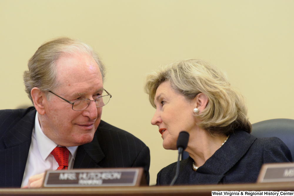 "[""Senators John D. (Jay) Rockefeller and Kay Hutchison talk during a Commerce Committee hearing.""]%"