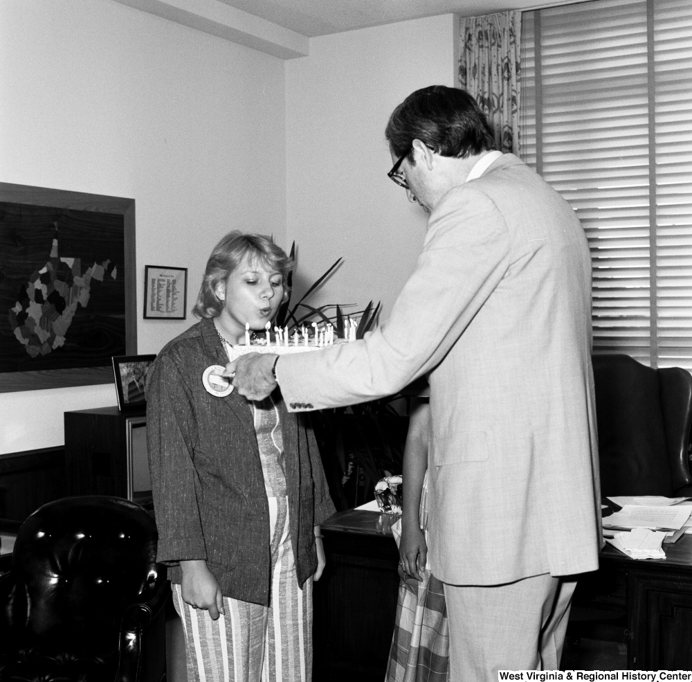 "[""Senator John D. (Jay) Rockefeller holds a cake as an unidentified individual from the Presidential Classroom for Young Americans blows out the candles in celebration of West Virginia's birthday.""]%"