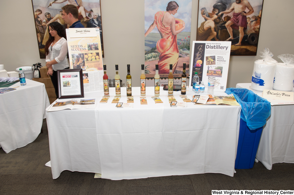 "[""A table of Sweet Shine liquors from Charles Town sits at the 150th birthday celebration for West Virginia.""]%"