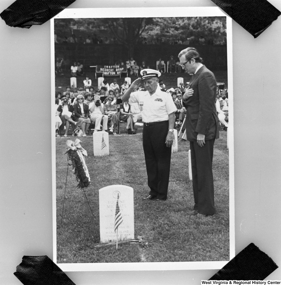 "[""This is a photograph of a photo where Senator John D. (Jay) Rockefeller stands with his right hand over his heart during a ceremony at Grafton National Cemetery in Grafton, West Virginia. This photograph was taken in July 1985, but it is impossible to determine when the original photo was taken.""]%"