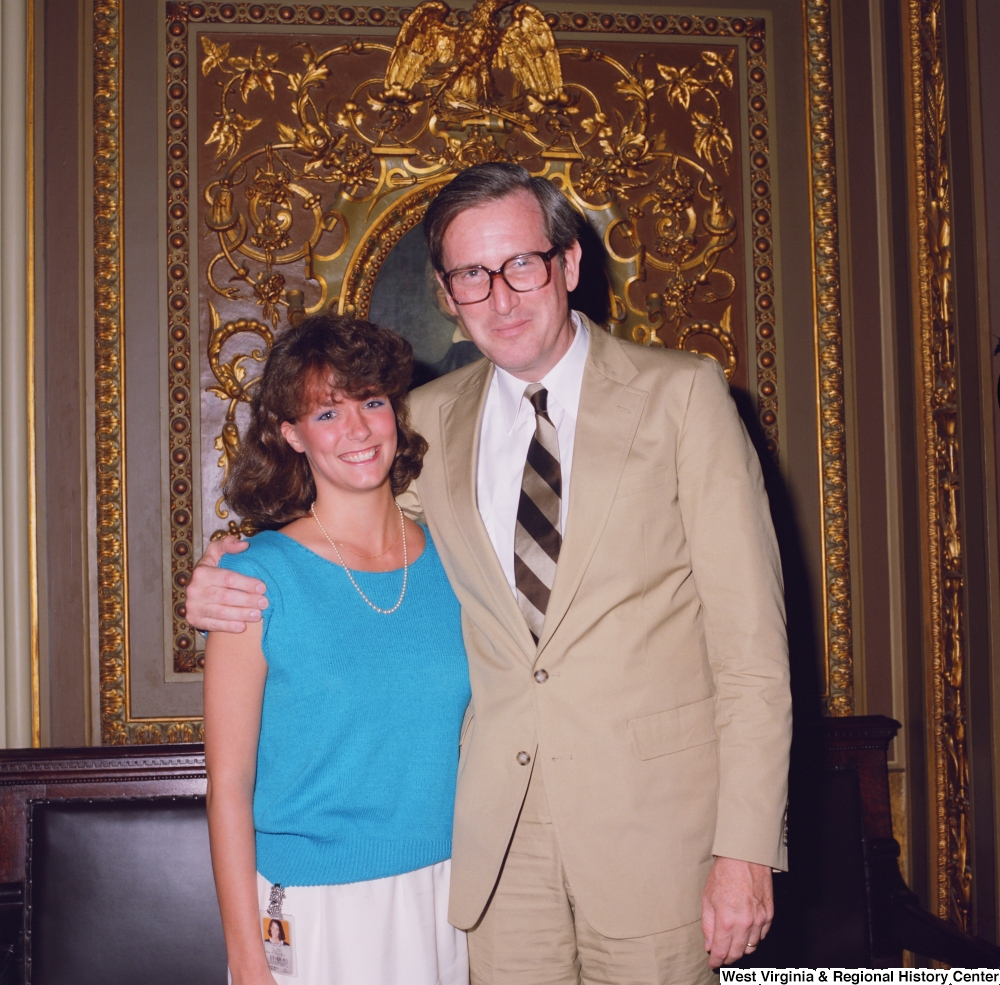 "[""Senator John D. (Jay) Rockefeller poses for a photograph with an unidentified woman in the President's Office outside the Senate.""]%"