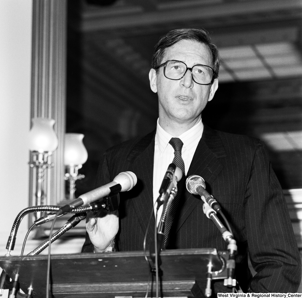 "[""Close up of Senator John D. (Jay) Rockefeller speaking at a press event in a Senate office building.""]%"