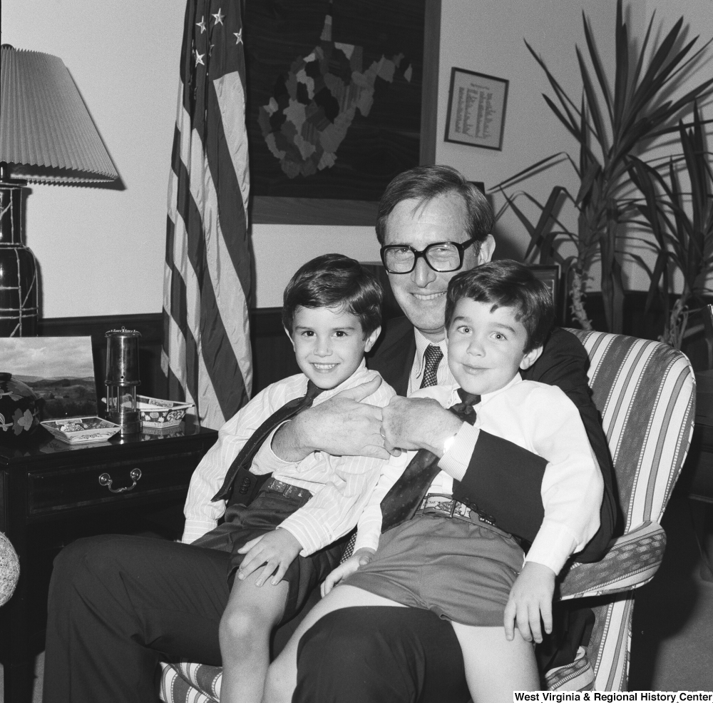 "[""Senator John D. (Jay) Rockefeller holds two unidentified young boys on his lap while he sits in his office.""]%"