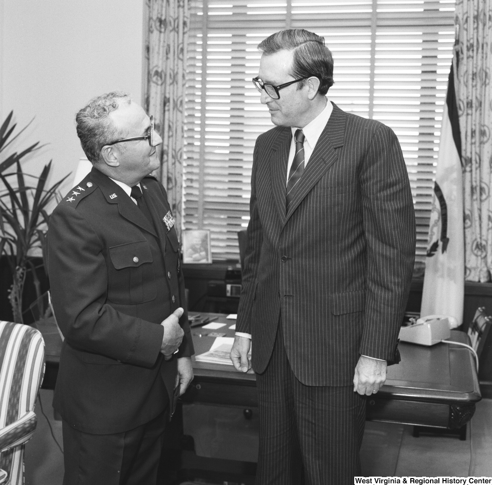 "[""Senator John D. (Jay) Rockefeller speaks with an unidentified military officer in his Washington office.""]%"