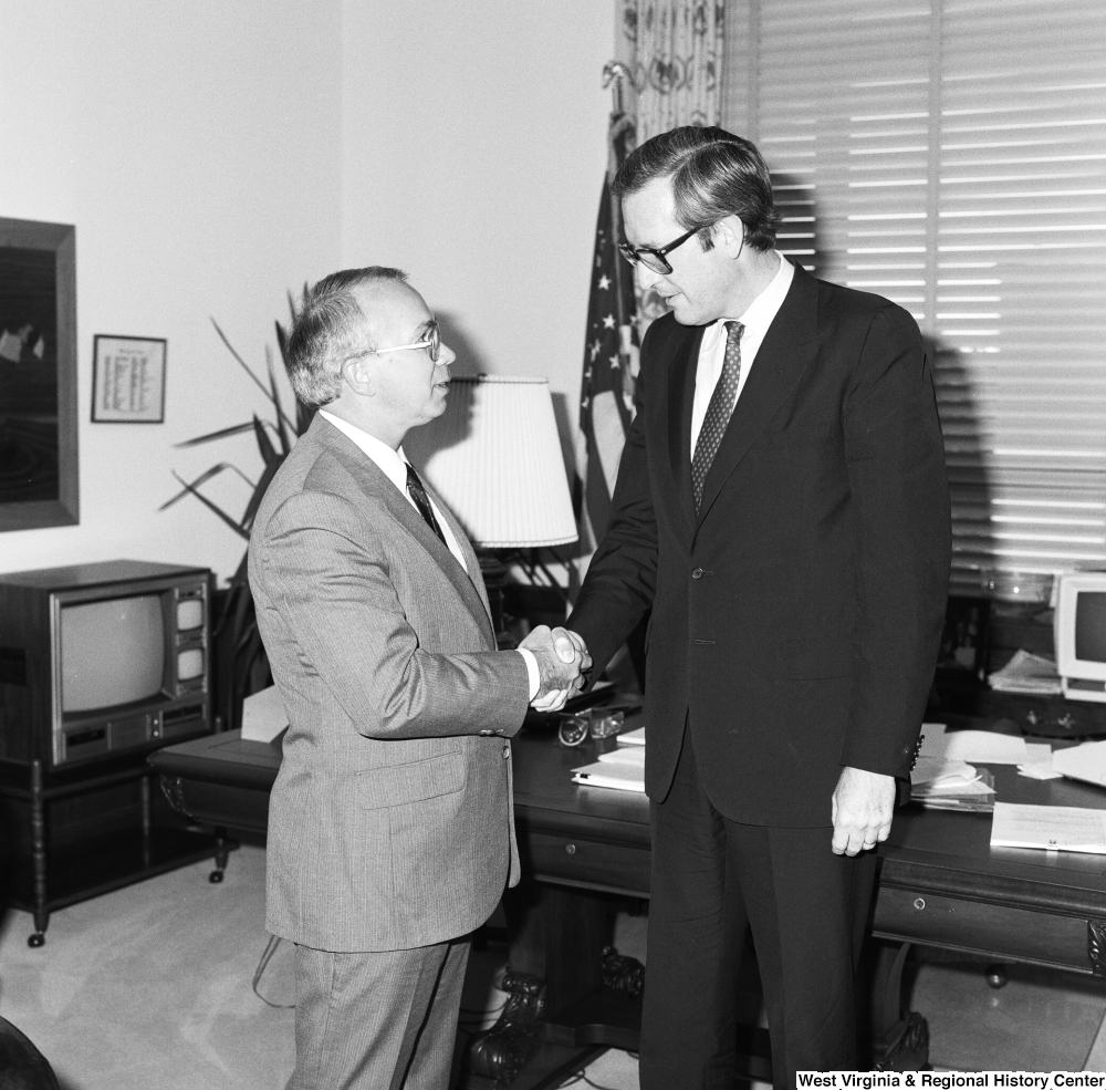 "[""Senator John D. (Jay) Rockefeller shakes hands with an unidentified guest in his Washington office.""]%"