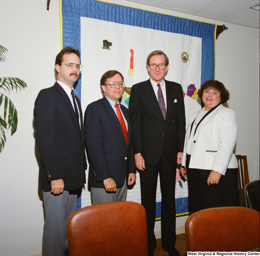 "[""Senator John D. (Jay) Rockefeller stands with three unidentified individuals in his office.""]%"
