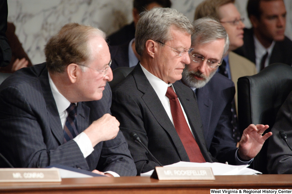 "[""Senator Max Baucus is briefed on an issue by an adviser during a Finance Committee hearing.""]%"