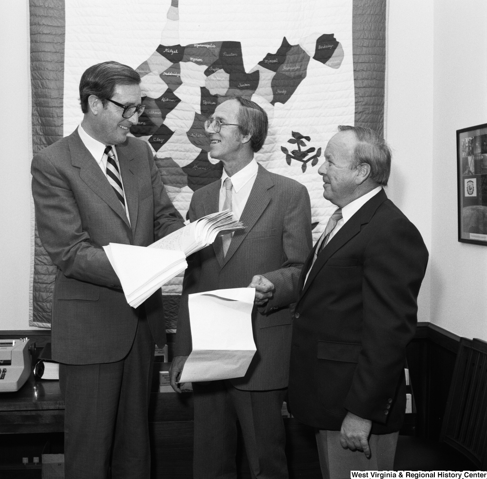 "[""Senator Rockefeller smiles and holds a stack of papers with the County Commissioner from Marshall County, West Virginia.""]%"