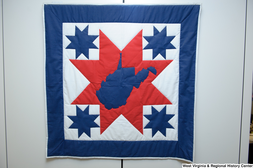 "[""A red, white, and blue West Virginia quilt hangs on a wall in Senator John D. (Jay) Rockefeller's office.""]%"