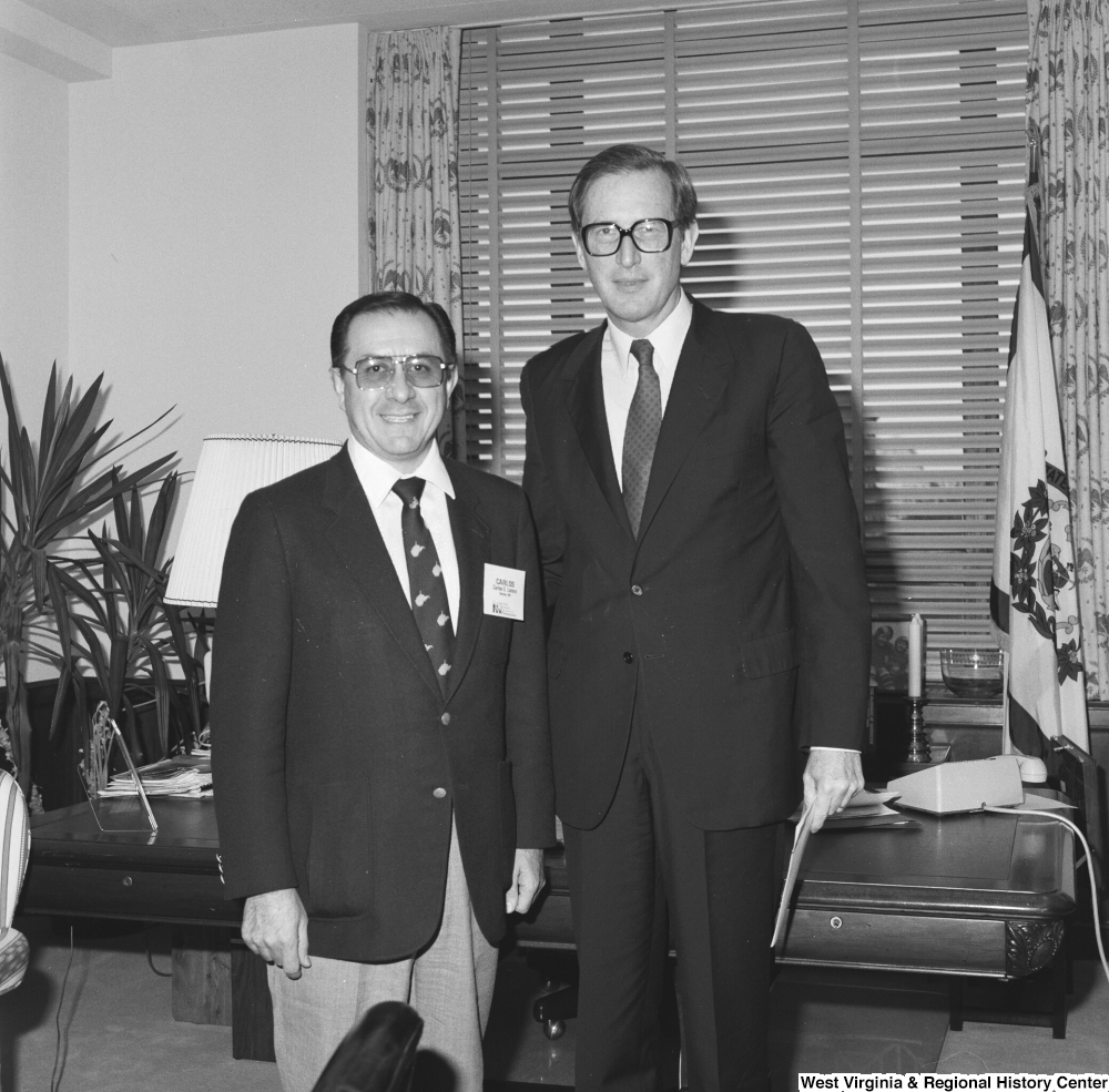 "[""Senator John D. (Jay) Rockefeller stands in his office with an unidentified individual.""]%"