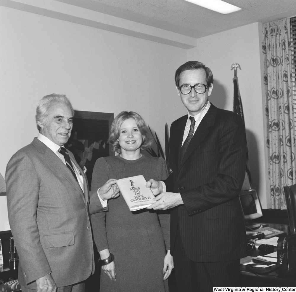 "[""Senator John D. (Jay) Rockefeller, his wife Sharon, and author Christopher G. Janus, a West Virginia native, hold a copy of the author's novel, \""Miss 4th of July, Goodbye\"". The novel is set in Montgomery, West Virginia and is based on the real-life experiences that Janus's sister had when she immigrated from Greece to West Virginia.""]%"