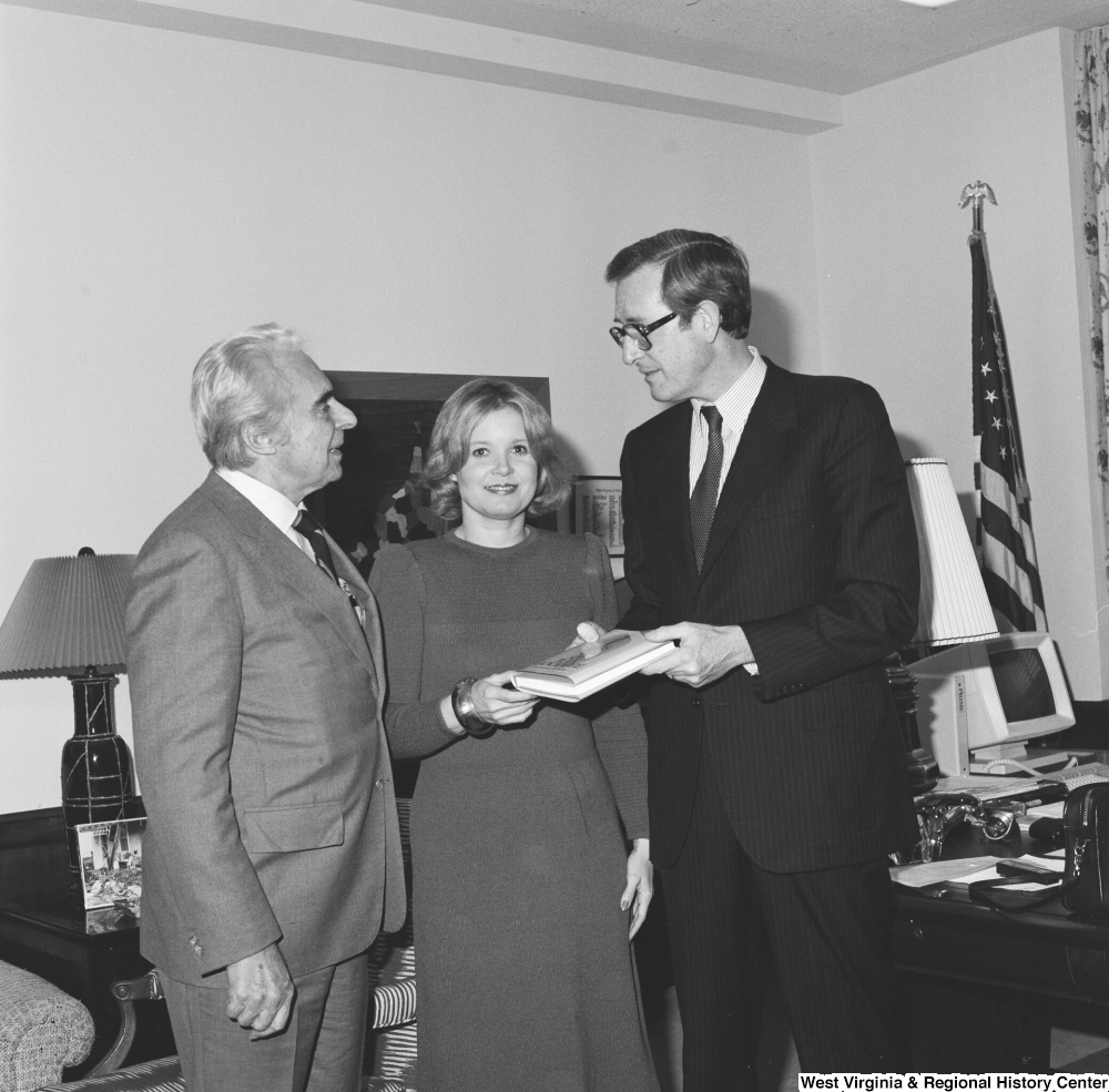 "[""Senator John D. (Jay) Rockefeller, his wife Sharon, and author Christopher G. Janus hold a copy of the author's novel, \""Miss 4th of July, Goodbye\"". The novel is set in Montgomery, West Virginia and is based on the real-life experiences that Janus's sister had when she immigrated from Greece to West Virginia.""]%"